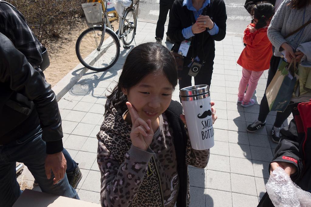 웰다잉 투어 기념품을 들고 환하게 웃는 어린이 모습